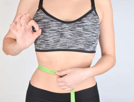 Fitness girl in sports tops measuring ruler waist on white background. The concept of losing weight.