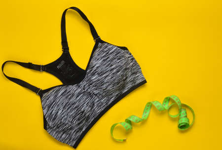 Sports female top and ruler for measuring body proportions on a yellow background. Sports concept. Top view.