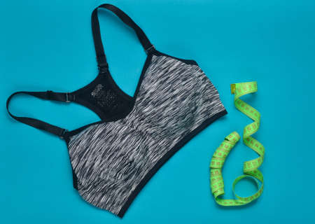 Sports female top and ruler for measuring body proportions on a blue background. Sports concept. Top view.