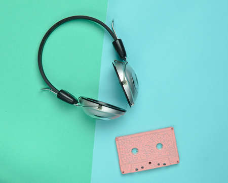 Wireless headphones and audio cassettes on a multicolored pastel paper background. Minimal creative art. Musical retro vibrations. Top view.