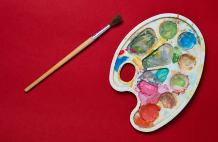Plastic palette with gouache paint and brush on a red paper background. Top view.