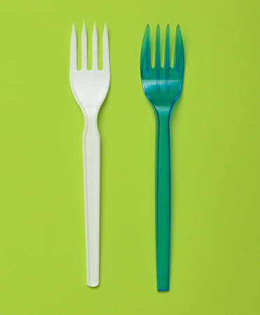 Plastic fork for a picnic on a green background. Minimalist trend. Top view.