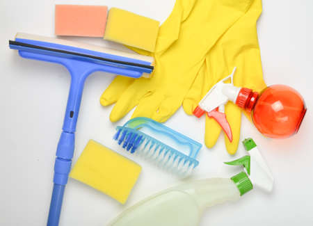 House cleaning products. Window mop, sponge, bottle of spray, yellow latex gloves, brush on white background. Top view. Flat lay style