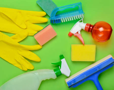 House cleaning products. Window mop, sponge, bottle of spray, yellow latex gloves, brush on green background. Top view. Flat lay style