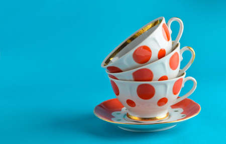 A stack of antique ceramic cups on a saucer on a blue background, copy space