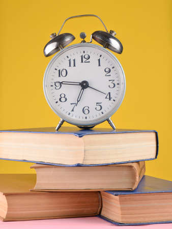 Alarm clock on top of piles of books on yellow background