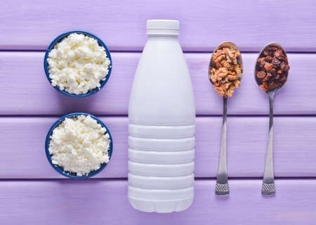 Healthy, dietary food. Morning breakfast. A bottle of yogurt, bowls with cottage cheese, spoons with walnuts and raisins on a violet wooden table. Top view. Flat lay food.