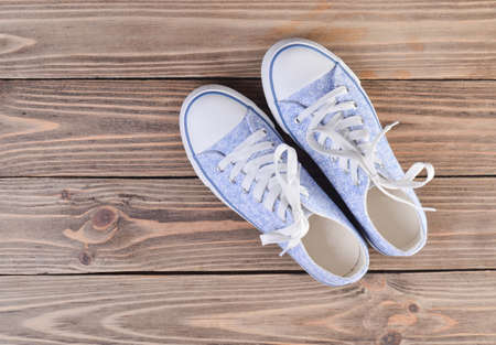 Female hipster sneakers with white laces on a pastel wooden floor, top view