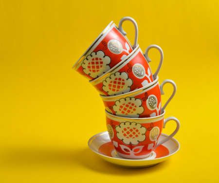 Stack of retro cups on a yellow background.