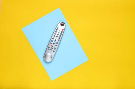 Tv remote on a blue yellow paper background. Top view. Minimalism. Copy space