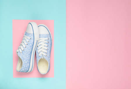 Fashionable female sneakers on a pink pastel blue background. Top View