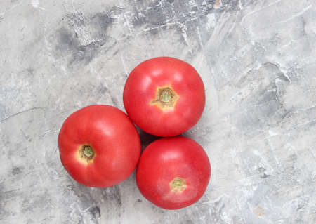 Three ripe tomatoes on a gray concrete background. Top view Stock Photo