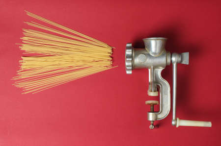 Vintage meat grinder and pasta on red background, top view, minimalism 免版税图像