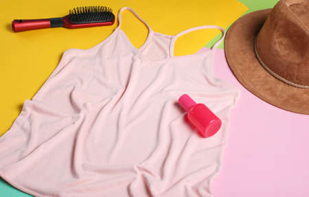 Women's fashion T-shirt, comb, hat, bottle of perfume on a colored pastel background. Minimalism, top view, flat lay