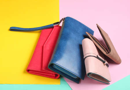 Many leather purses on a colored pastel background. Top View