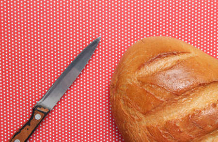 Loaf of bread, knife on a red tablecloth in polka dots, top view
