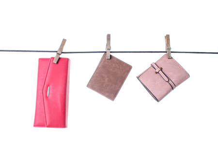 Different leather wallets are hanging on the clothesline with the buckles. Isolated on white background.