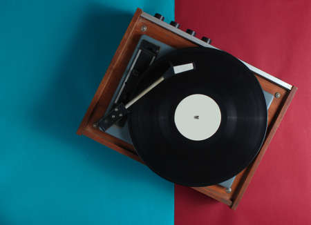 Retro vinyl record player on red-blue background. Top view