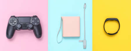 Power bank and usb cable, gamepad, smart bracelet on colored pastel background. Modern gadgets. Top view, minimalism.