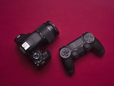 gamepad and dslr camera on burgundy red background
