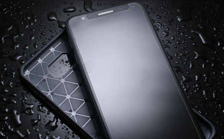 Smartphone with protective cover on black background with water drops. Protect your smartphone from water