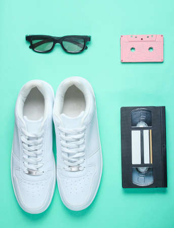 Pop culture, retro style. White hipster sneakers, audio and video cassette, 3D glasses on a mint-colored paper background. Top view