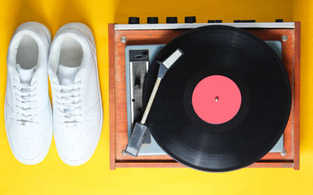 Pop culture. White hipster sneakers, vinyl player on a yellow background. Retro style. 80s. Top view, minimalism