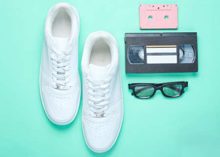 80s, retro style. White hipster sneakers, audio and video cassette, 3D glasses on a mint-colored paper background. Top view