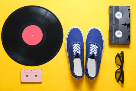 Pop culture. Hipster sneakers, vinyl plate, audio and video cassette, 3d glasses on yellow background. Retro style. Top view, minimalism