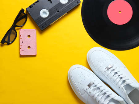 Pop culture. White hipster sneakers, vinyl plate, audio and video cassette, 3d glasses on yellow background. Retro style. Top view, minimalism. Copy space