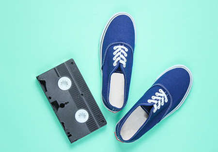 Retro sneakers, video cassette on blue background. Pop culture,80s, top view