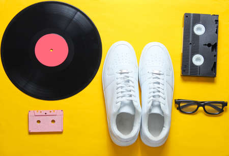 Pop culture. White hipster sneakers, vinyl plate, audio and video cassette, 3d glasses on yellow background. Retro style. Top view, minimalism