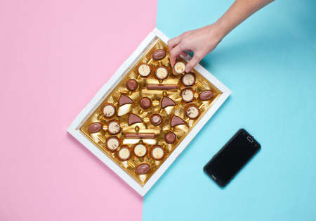 Girl takes a chocolate candy from a box of chocolates with a golden tray on blue pink pastel background. Top view, minimalism Stock Photo