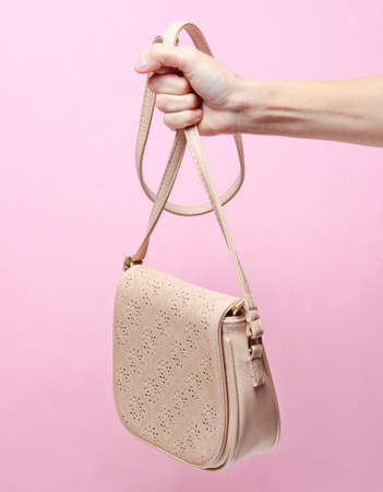 Female hand holding leather trendy bag by the strap on pink pastel background. Minimalism