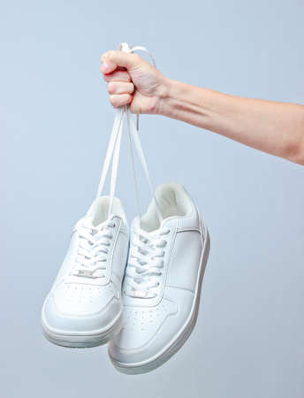 The hand holds by shoelaces hipster white sneakers on gray background. Minimalism