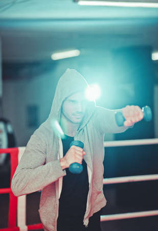Boxing concept. Boxer man during boxing exercise making direct hit with dumbbells in boxing ring