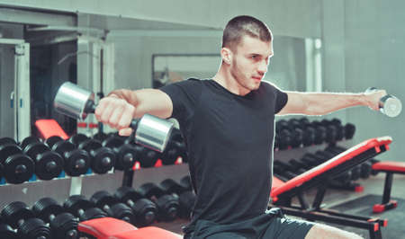 Athletic young man exercising his shoulders and doing side raises with pair of dumbbells at gym