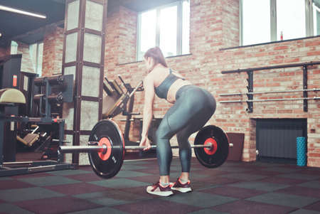 Muscular young fitness woman doing heavy deadlift exercise at gym Back view.