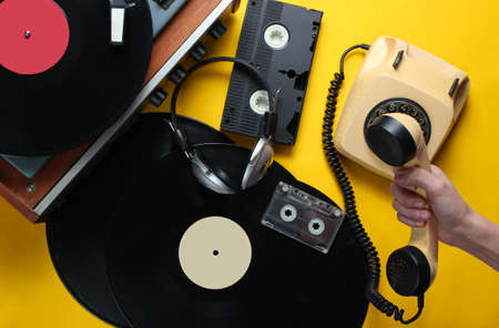 Retro attributes from the 80s on yellow background. Female hand holds the handset of vintage rotary phone against the background of vinyl player, video, audio cassettes, headphones. Top view