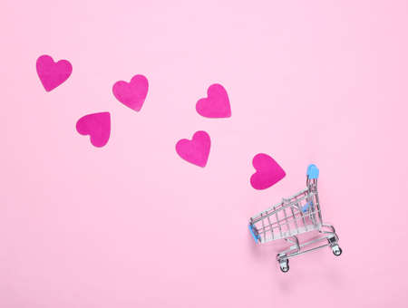 Mini shopping trolley, decorative hearts on a pink background, top view, minimalism. Conceptual photo