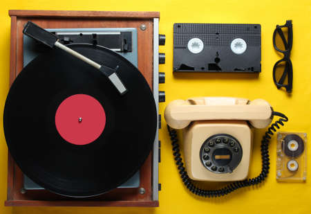Old-fashioned objects on yellow background. Retro style, 80s, pop culture. Top view. Vinyl player, rotary phone, video, audio tape