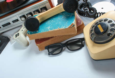 Retro 80s pop culture media objects on white background. Copy space. Sneakers, rotary phone, vinyl player, old books, audio, video tapes, 3d glasses, gamepad.