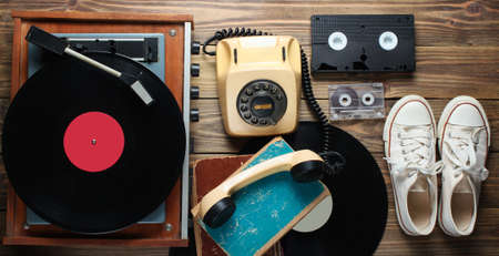 Obsolete objects on wooden background. Retro style, 80s, pop media