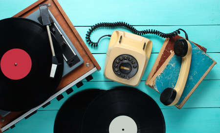 Vinyl player, rotary phone, vinyl plates, old books. Old-fashioned objects on a blue wooden background. Retro style, 70s. Top view.