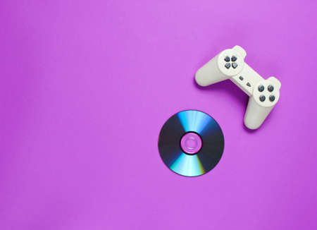 CD's disk, gamepad on a purple background. Retro gaming. Pop culture 80s. Top view, minimalism