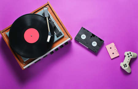 Retro items on a pink background. Vinyl player, video, audio cassette, gamepad. Pop culture, 80s. Top view