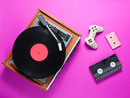 Retro items on a pink background. Vinyl player, video, audio cassette, gamepad. Top view