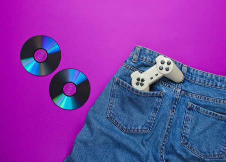 Pop culture gadgets on the purple paper surface. Retro gamepad in denim jeans pocket, Cd's, top view