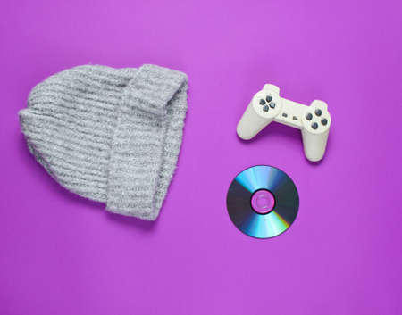 CD disk, gamepad, warm hat on a purple background. Pop culture 80s. Top view, minimalism