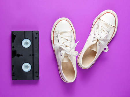 Pop culture attributes 80s. Retro white sneakers shoes, videotape on a purple background. Top view